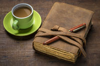 antique leather-bound journal on rustic wood with coffee