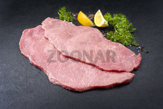 Raw veal schnitzel from topside as closeup on black background with copy space