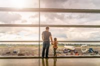 Silhouette of young family, father and daughter on airport terminal