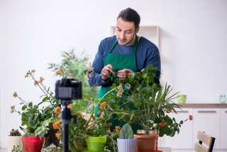 Young male gardener with plants indoors