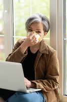 Mature woman in protective fp1 face mask working on laptop compute sitting on a windowsill at free woking zone or workstation. A beautiful aged woman runs her own business as a freelancer