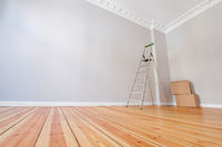 empty room after renovation with ladder and cardboard boxes -