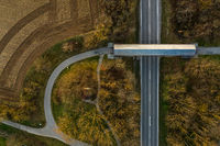 Top view from a drone at a road with a bridge and a curved road at autumn.