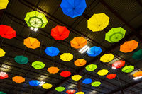 Brightly colored umbrellas hanging from metal ceiling of warehouse space
