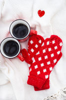 Romantic still life, two red cups of coffee on a white plaid together with red mittens. Valentine's day concept, card ready.
