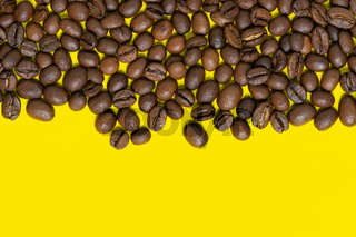 Brown coffee beans on yellow background. Top horizontal location objects, copy space for text at bottom. Flat lay, close-up view of coffee still life