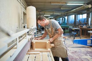 Tischler bearbeitet Holz mit der Schleifmaschine