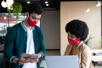 Diverse businessman and businesswoman wearing face masks using tablet in office