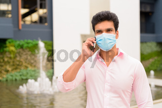 Young Indian businessman with mask talking on the phone in the city outdoors