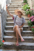 Beautiful female tourist wearing big straw sun hat and shorts sitting and relaxing on old stone house stairs during summer travel on Mediterranean cost on hot summer day and taking selfie