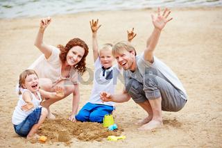 Familie jubelt im Sommer am Strand