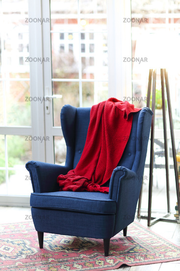 Elegant blue armchair with red plaid in room