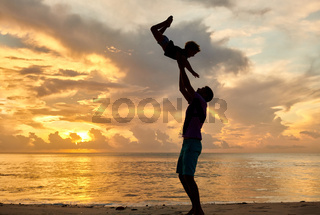 Father throws up son in the air on beach at sunset