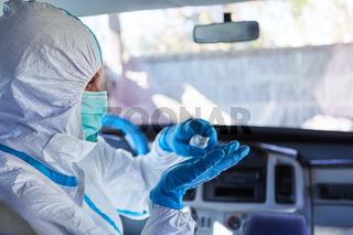 Putzkraft trägt Desinfektion in Innenraum von Rettungswagen auf wegen Coronavirus