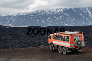 Expedition truck on mountain road on background lava fields and Kamchatka Peninsula volcanoes