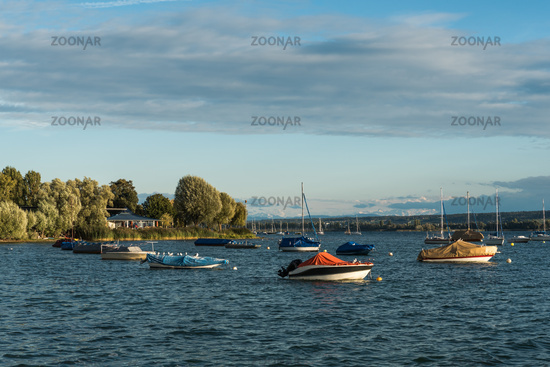 View from the shore in Allensbach to Lake Constance with boats and Alps, Baden-Wuerttemberg, Germany
