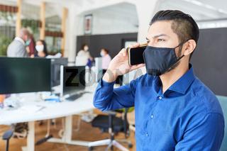 Business Mann mit Mundschutz telefoniert mit Smartphone