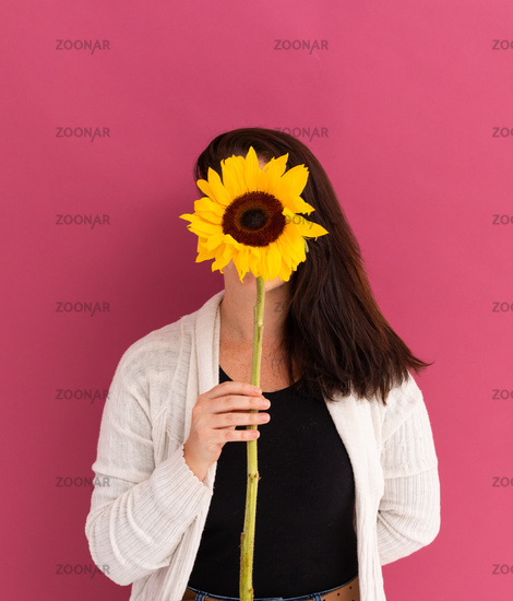 Caucasian woman covering her face with sunflower on pink background