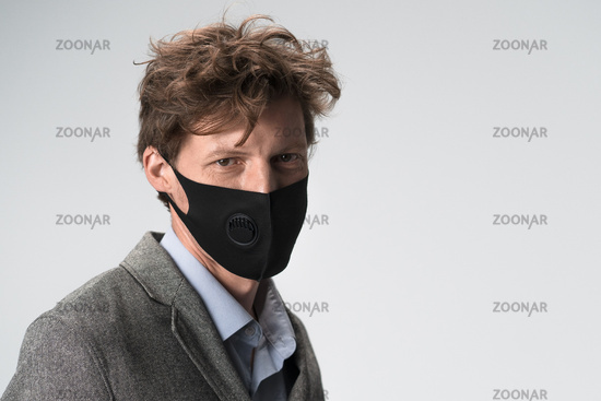 Modern serious man in black face mask on white background. Head and shoulders portrait