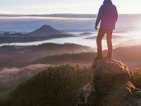 Man stay on sharp rock peak above heavy mist