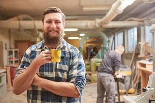Hipster Schreiner mit Bart macht eine Kaffeepause