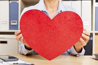 Frau hält ein rotes Herz