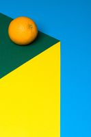 Fruit of orange on a multicolored background, halves of oranges on colored paper. Copy space.