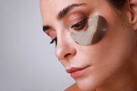 Close-up of beautiful caucasian woman with hydrogel eye patch isolated on white.