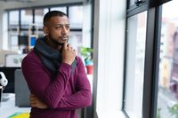 Mixed race businessman in thought looking through window in creative office