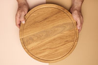 male hands holds round empty wooden pizza board, brown background