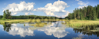 Blue mirror lake reflections of clouds and landscape. Sudbury, Ontario, Canada.