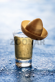 Gold tequila shot with a sombrero. One glass of tequila with salt