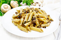 Pasta with mushrooms in white plate on board
