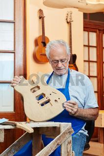 Mann als Gitarrenbauer in Werkstatt mit Gitarre