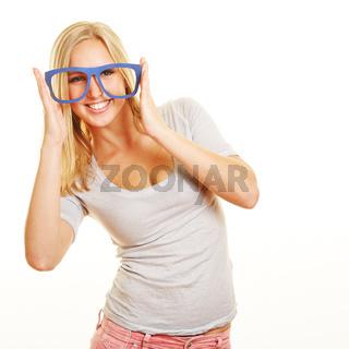 Lachende Frau mit Nerd-Brille vor Gesicht