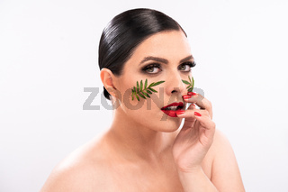 Beauty woman. Beautiful female model with perfect clean fresh skin with green leaves patches on her face. Skin care treatment or cosmetic ads concept. Isolated on white background