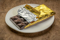 chocolate bar on plate being unwrapped