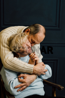 portrait of old couple wife and husband hugging and smiling. Dark blue background. Happy lovers on retirement. Stop ageism.