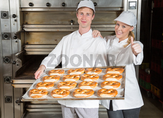 Bakers with baking tray in bakery showing thumbs up