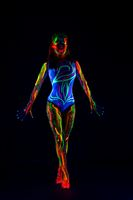 Female model with colorful ultraviolet body in dark