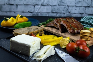 Ribs under honey sauce on a wooden board next to tomatoes, sliced feta with cracker. Top views