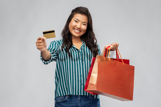 asian woman with shopping bags and credit card