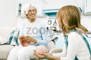 Grandmother having lovely conversation with her granddaughter while knitting