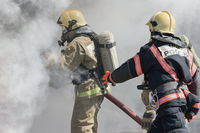 Firefighters extinguishes fire from fire hose, using firefighting water-foam barrel