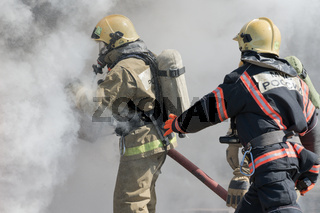 Firefighters extinguishes fire from fire hose, using firefighting water-foam barrel with air-mechanical foam