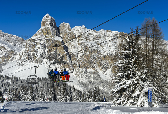 Skiers on a chair lift against snow-covered Mount Sassongher, Alta Badia, Dolomites, Italy