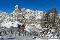 Skifahrer auf einem Sessellift vor dem verschneiten Gipfel Sassongher