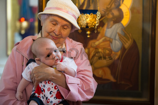 Belarus, Gomel, May 6, 2018. Church of Volotovo. Baptism of a newborn child.Old grandmother in church with grandson in hands of the icon of theotokos