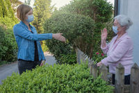 Senior woman with face mask keeps distance to neighbor woman