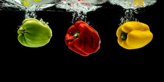 Three colourful bell pepper or paprika falling into the water.